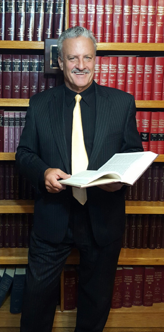 Neil L. Calanca standing next to a book case.